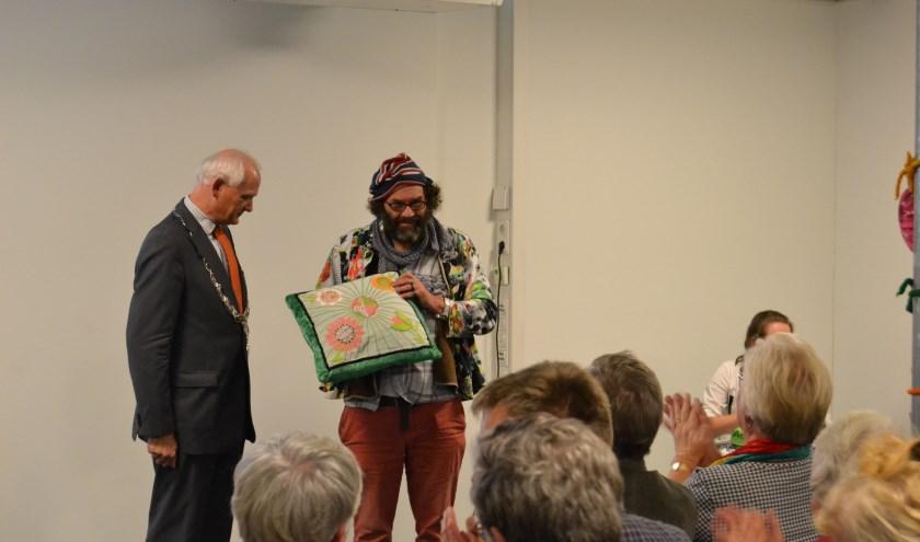 Vrijwilliger Hans Brinkman toont het kussen, dat hij als steuntje in de rug zojuist van burgemeester Lamers heeft gekregen.