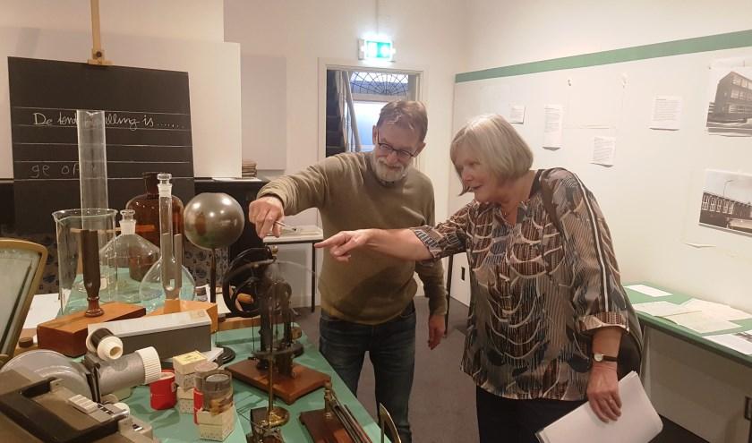 Jack Bogers en Ditta van Vliet bekijken de spullen in het oude natuurkundelokaal. (foto: Kees Stap)