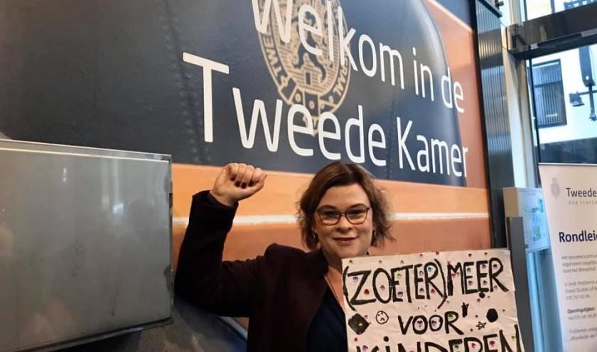Wethouder Jakobien Groeneveld met haar protestbord dat ze bij binnenkomst moest inleveren van de beveiliging. Foto: Privécollectie