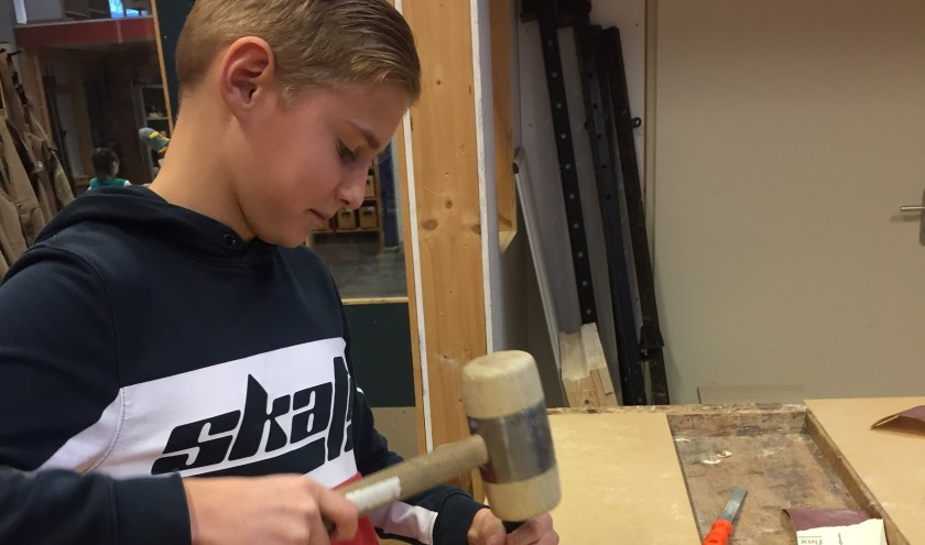 Thomas uit groep 8 maakt een houten dobbelsteen. (Foto: CSG De Lage Waard)