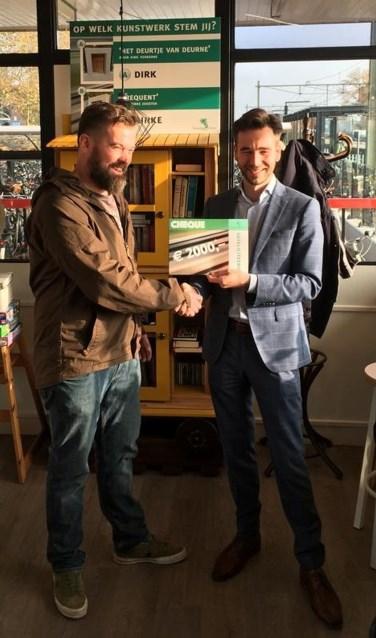 Kunstenaar en ontwerper Dirk Verberne krijgt de cheque uit handen van wethouder Biemans.