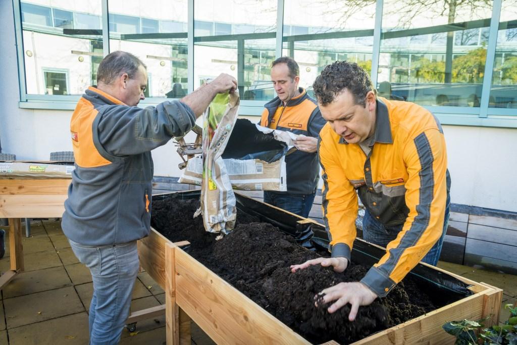 Vrijwilligers vullen de kweekbakken met aarde en zaadjes. Deze lente kan er dus meteen getuinierd gaan worden. (foto: PR)   © DPG Media