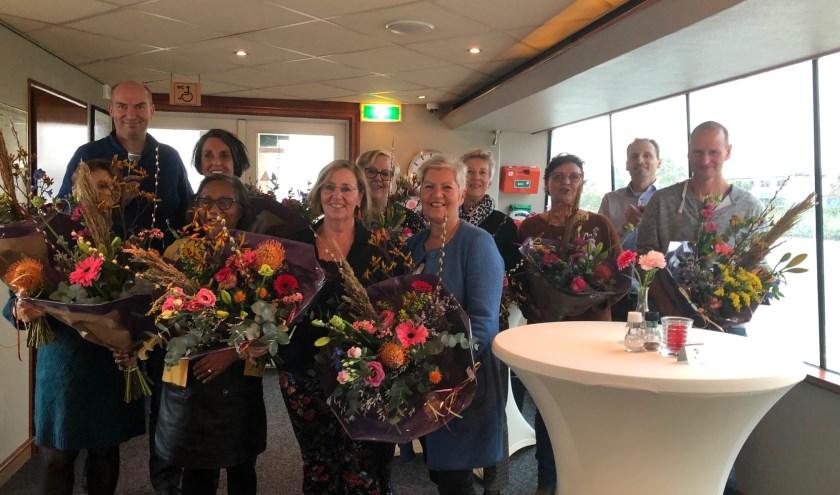 Bloemen werden overhandigd aan de vrijwilligers door twee bestuursleden van MooiWonenInEnspijk Martijn Karrenbeld en Guido van der Wedden.