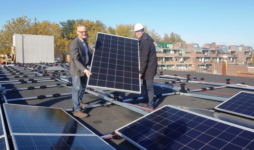 Ruud van Doorn van HEMA Wageningen en wethouder Peter de Haan met 1 van de 260 zonnepanelen. (foto: Kees Stap)