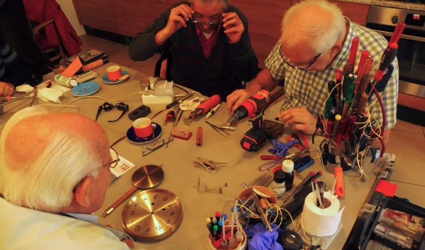 Impressie van het Repair Café. Bezoekers en vrijwilligers herstellen samen kapotte spullen.