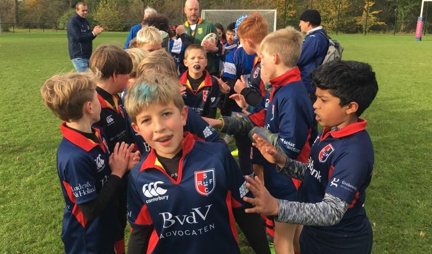 De jeugdspelers van de Stichtsche Rugby Club lopen na de wedstrijd tevreden door de traditionele rugbypoort