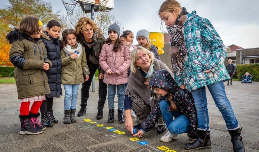 De leerlingen van basisschool krijgen in de gezonde buitenlucht spelenderwijs rekenles van juf Michelle en directrice Elly Sebregts (gehurkt). Foto: Yuri Floris Fotografie