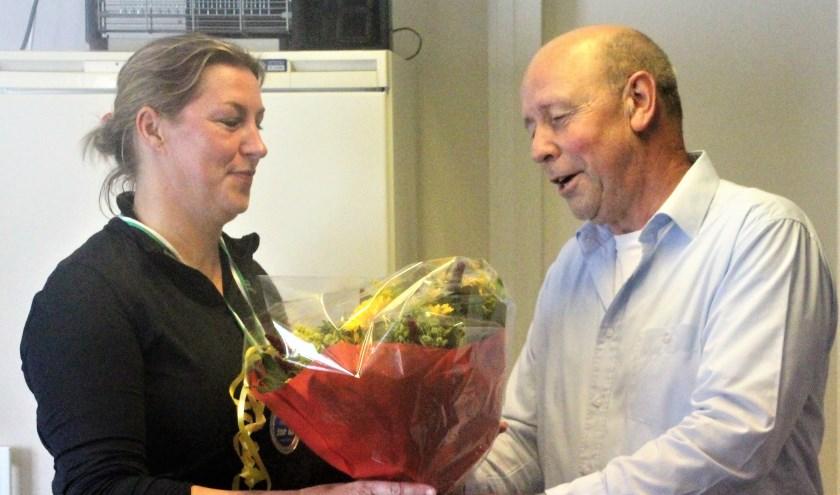 Voorzitter Hennie van Rijt zet Angeliek Willems, het 300e lid van Atletiek Oirschot in de bloemen.
