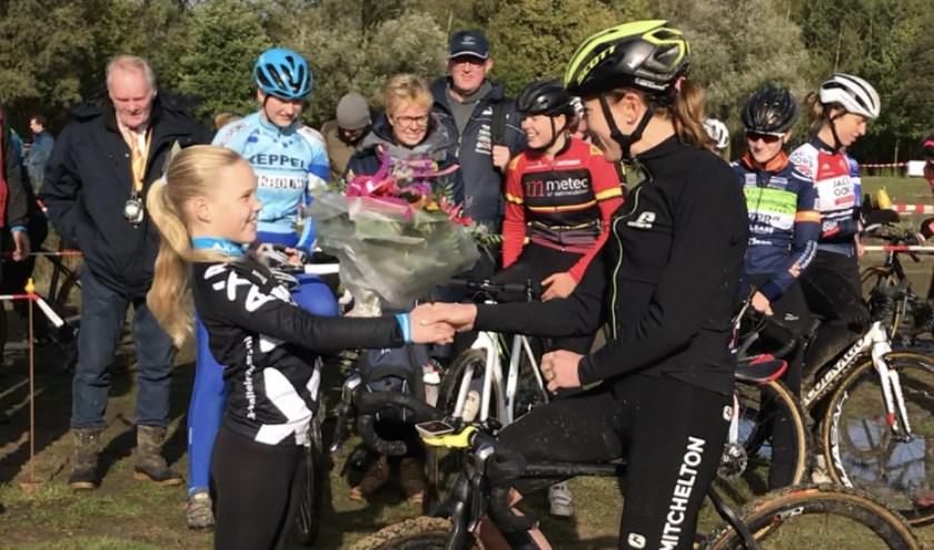 Carmen van den Boogaart mag aan haar idool Annemiek van Vleuten bloemen overhandigen.