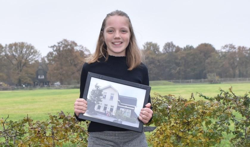 Roos Kamphuis met de foto van alle deelnemers voor het huis in Aalsmeer. (Foto: Van Gaalen Media)