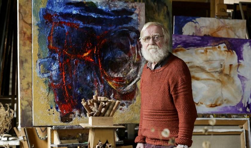 Kunstschilder Theo Kappé in zijn atelier met op de achtergrond één van zijn vele schilderijen. (Foto: Jurgen van Hoof).