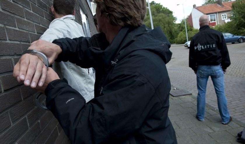 Agent drukt verdachte tegen muur om boeien om te doen.