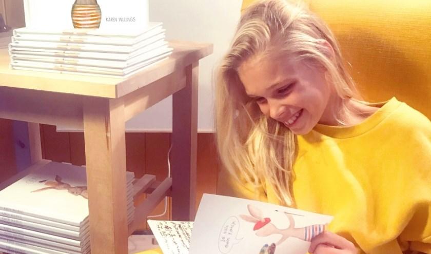 Lenthe leest het boek Gein Konijn van haar moeder Karen Wullings. Al doorbladerend kon ze om het boek lachen, een goed teken.