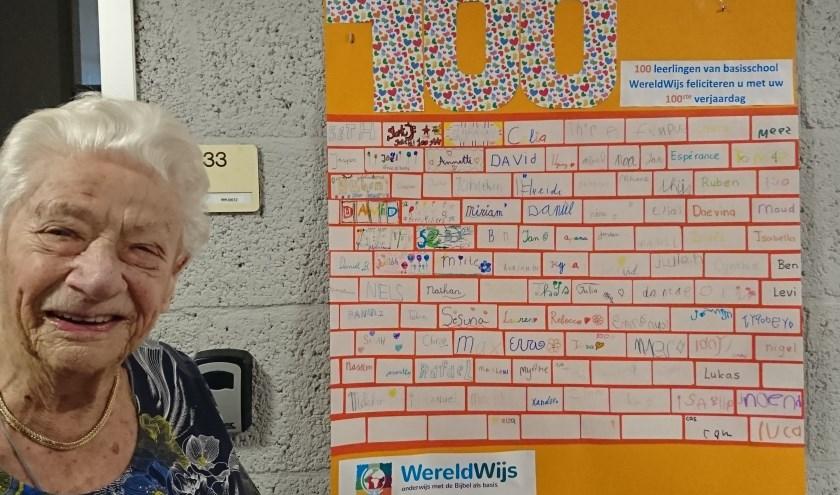 mevrouw Dietz bij de felicitatieposter van basisschool Wereldwijs