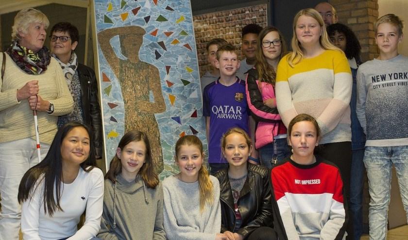 Leerlingen van het van Haestrechtcollege poseren bij het mozaïekkunstwerk 'Meisje kijkt naar de horizon, met blik op de toekomst'. Foto: Stef Mennens/Drieluik Fotografie