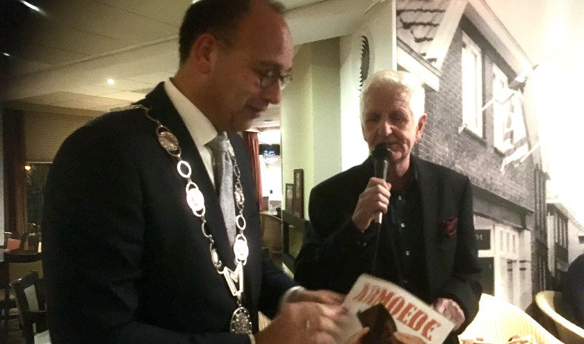 De burgemeester ontvang het eerste exemplaar van de brochure over armoede die deze week bezorgd wordt. (foto: Karin van der Velden)