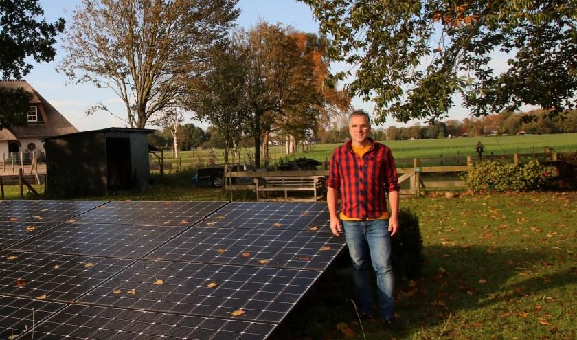 Louis van Andel bij de zonnepanelen waarmee de warmtepomp van stroom voorzien wordt. (foto: Elsie Schoorel)