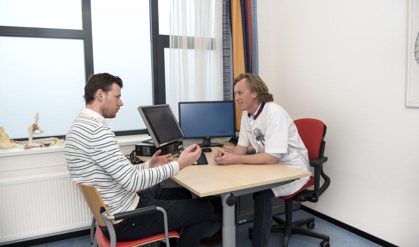 Een patiënt in gesprek met traumachirurg Piet Hoek over een passend behandelplan.