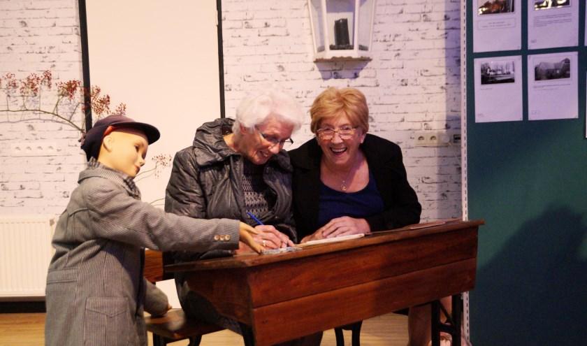 Vriendinnen Chrisje de Graaf en Annie Lievaart halen herinneringen op tijdens de opening van de tentoonstelling.