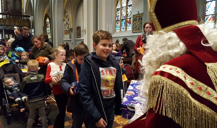 Kinderen brengen cadeaus naar de Sint.