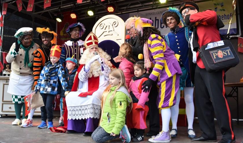 Sinterklaas te midden van zijn pieten, kinderen en rechts Jan Kooreman (met microfoon)