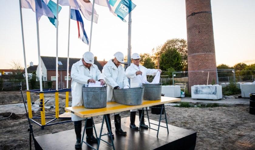 Wethouder Marcel Willemsen en twee toekomstige bewoners tijdens de officiële handeling. Een ode aan de geschiedenis van de locatie. (foto: Peter Lodder)