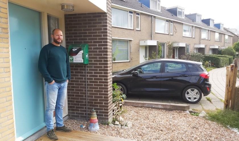 Ruud te Winkel bij zijn huis in de Abbé St Pierrelaan met de AED aan de muur.  Foto: Theo Rietveld