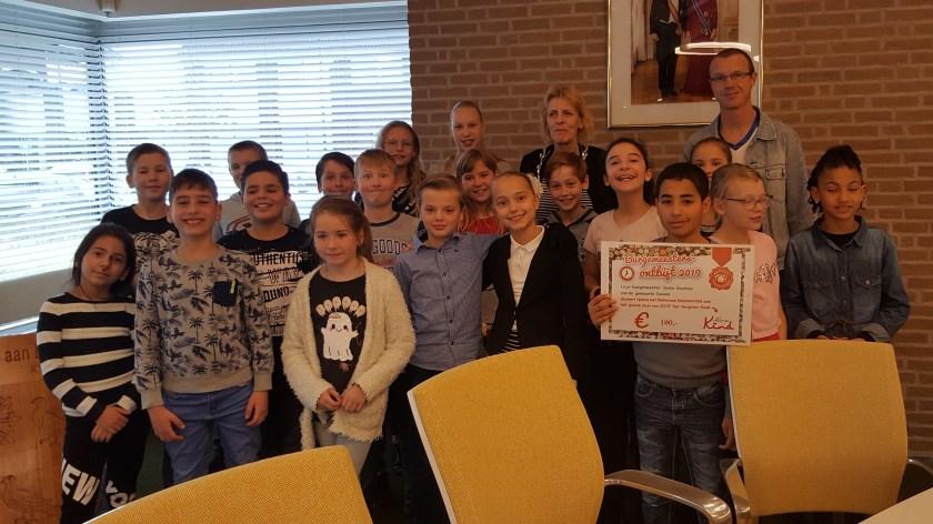 Locoburgemeester Ineke Knuiman (achteraan in het midden) en de leerlingen van basisschool De Wereldwijzer, met wie ze in het gemeentehuis ontbeet.