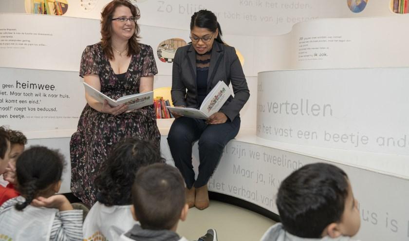 Jeugdwethouder Kavita Parbhudayal (rechts) en auteur Femke Beeloo-Planken lezen voor uit het nieuwe kinderrechtenboekje;