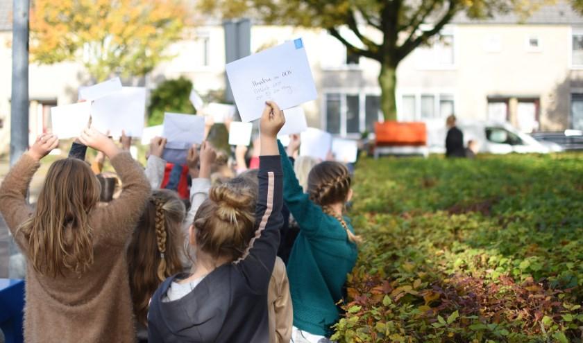 De kinderen staan in de rij om hun brief voor de minister te posten.