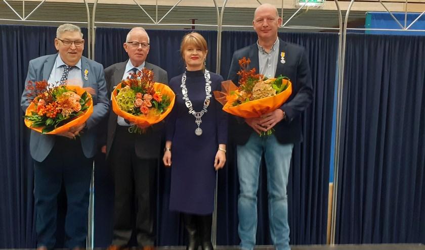 Burgemeester Cia Kroon tussen de drie mannen die een koninklijke onderscheiding hebben gekregen.