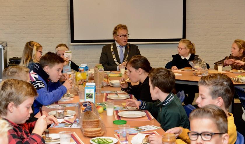 Burgemeester Keereweer tijdens Het Nationaal Schoolontbijt met de leerlingen van de Eben Haezerschool uit Waardenburg.