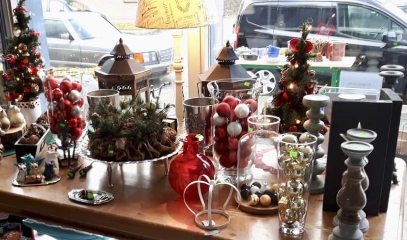 De etalage van de kringloopwinkel geeft een impressie van wat er in de winkel is te verkrijgen aan kerstartikelen.