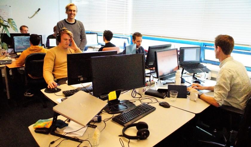 Tom van Loef tussen zijn team op de twaalfde etage van de TU Delft. Foto: Robbert Roos