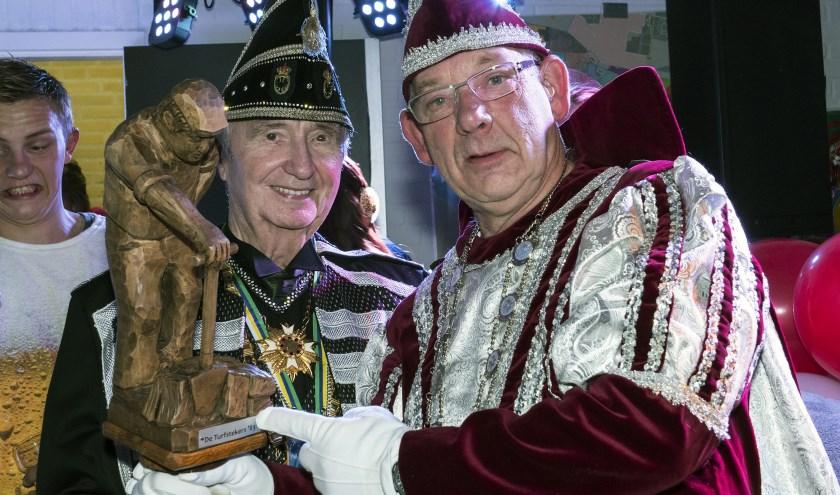Willem Dekker krijgt uit handen van Tonny Leerink (links) een onderscheiding nadat hij is gekozen tot prins van De Turfstekers. (foto Auke Pluim)