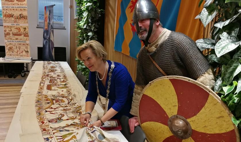 Onder het toeziend oog van ridder Kees, steekt burgemeester Annemiek Jetten de laatste steek op het eerste deel van het Tapijt van Vlaardingen.