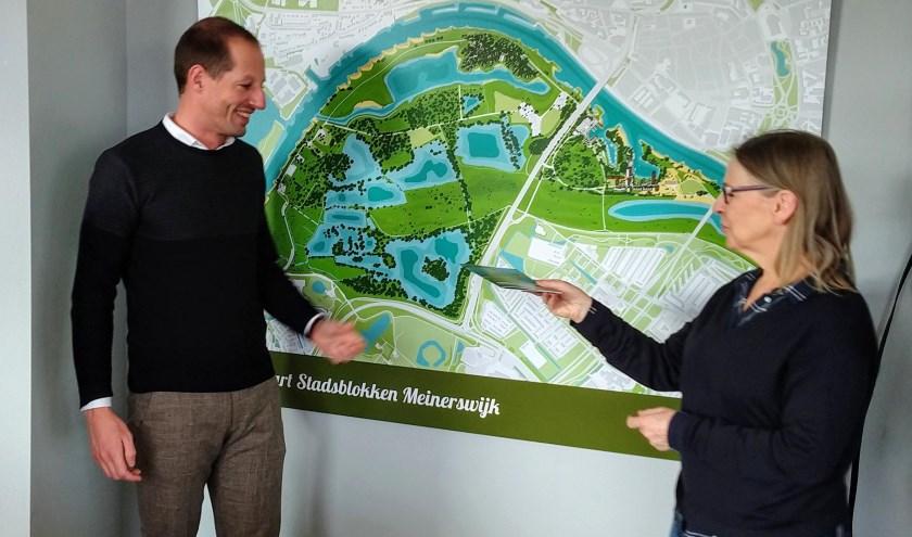 Roy Nijenhuis van KondorWessels neemt het eerste exemplaar van 'Parkenwijzer Meinerswijk' in ontvangst van Loes Meeuwissen, auteur van het boekje. (foto: Gerard Herbers)