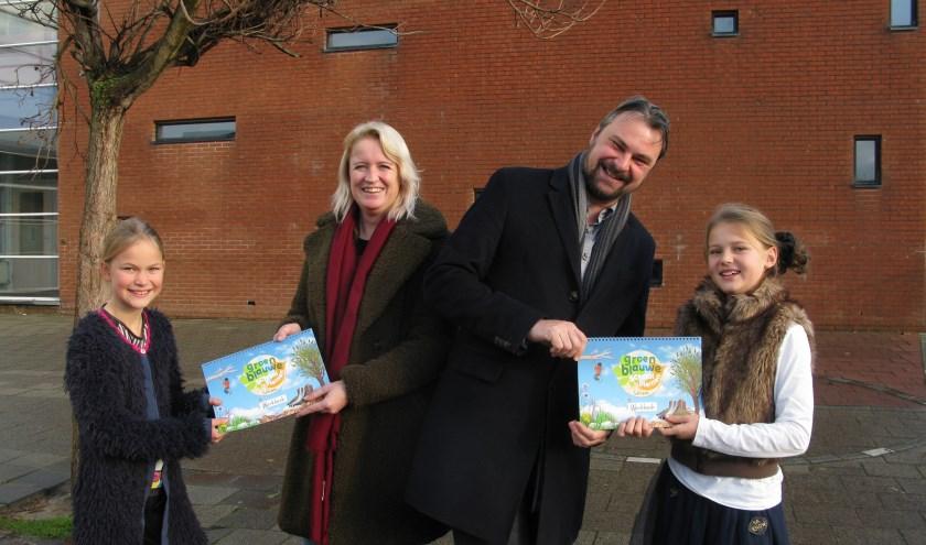 Twee leerlingen van obs De Violier overhandigen het werkboek 'Groenblauwe schoolpleinen' aan wethouders Van Aaken (2e van links) en Jeroen Ooijevaar (2e van rechts)
