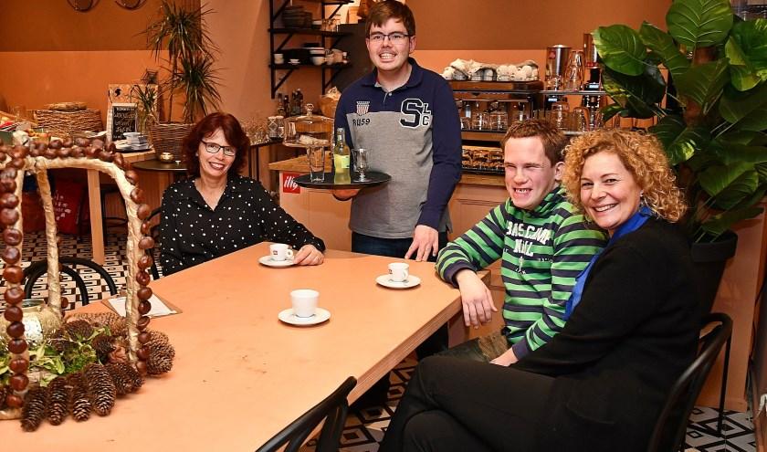 Oscar (midden) vindt het erg gezellig in het Café Riche in Roemrijck. Rechts zit medebewoner Joey. De dames zijn de woonbegeleiders. (foto: Ab Hendriks)