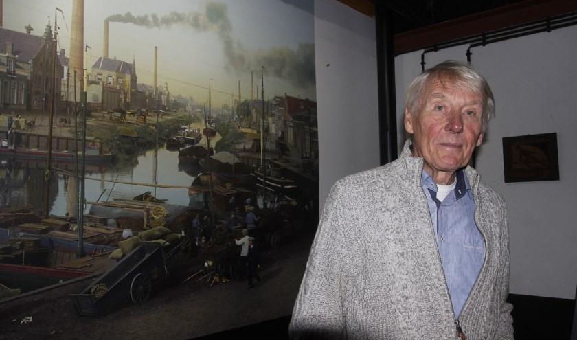 Piet Vogelzang in zijn pand bij de foto waar Almelo uit de begin jaren 1900 staat afgebeeld