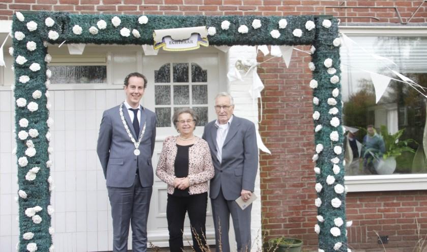 Het echtpaar samen met loco-burgemeester Arjen Maathuis onder de boog die de buren geregeld hebben