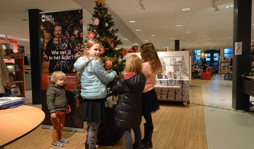 Luuk Korteweg en Nynke, Bente en Eline van Belkum hangen hun bal in de boom in de bibliotheek in Zaltbommel. Tot en met 24 december kun je nog een kerstbal met kerstgedachte ophangen in de bieb.