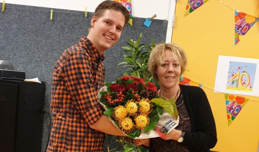Juf Marja van Vuure neemt bloemen in ontvangst van directeur Patrick van den Hoorn
