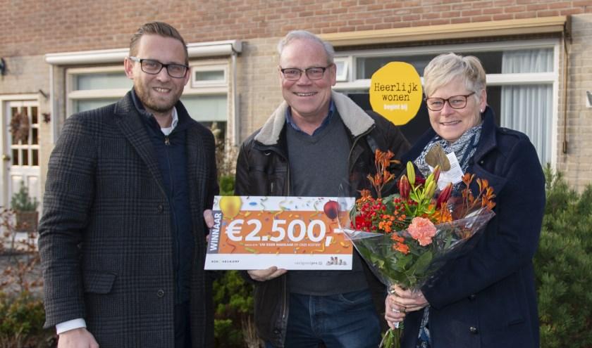 Makelaar Nico van der Heiden (l.) van Kok & Heijkamp Makelaars overhandigt de cheque ter waarde van 2.500 euro aan familie Dikken.