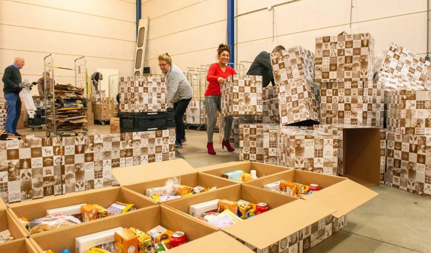 Leden van de Rotary Epe en Inner Wheel Epe zijn bezig om kerstpakketten in te pakken voor gezinnen die wel een extraatje kunnen gebruiken. Foto: Dennis Dekker