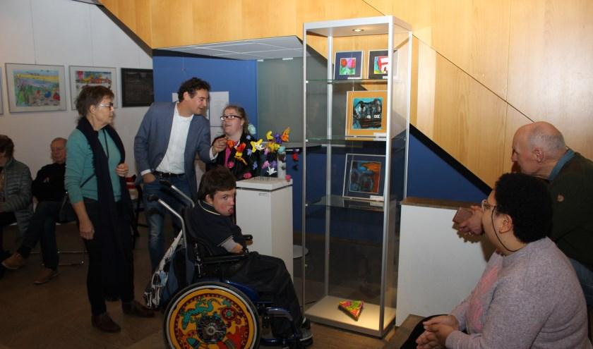 De officiële opening: Tiuri Kunneman (in de rolstoel) drukt op de knop en het licht van de vitrine gaat aan zodat de kunstwerken zichtbaar worden. (Foto's: Pieter Vane(