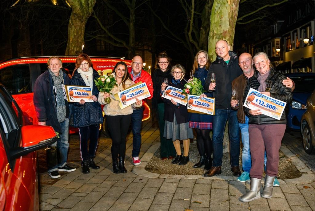 Inwoners uit Schiedam worden verrast door Postcode Loterij-ambassadeur Gaston Starreveld met de PostcodeStraatprijs-cheque.  © DPG Media