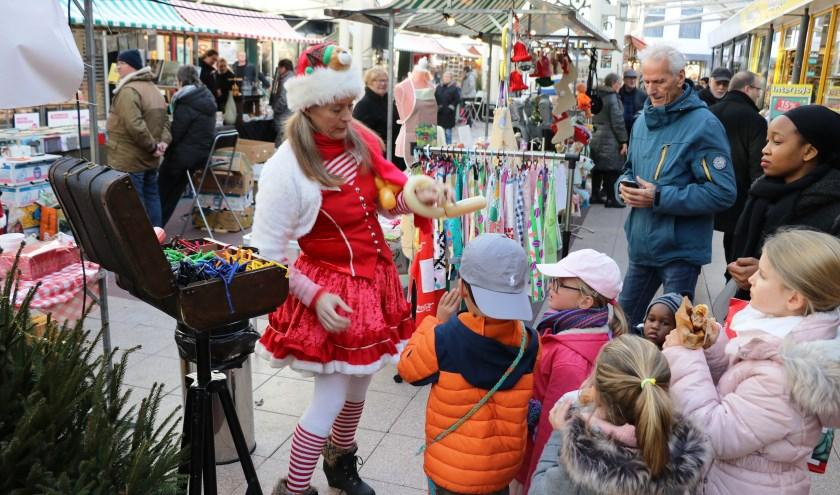 De kerstvrouw maakt ballonnencreaties voor alle kinderen.