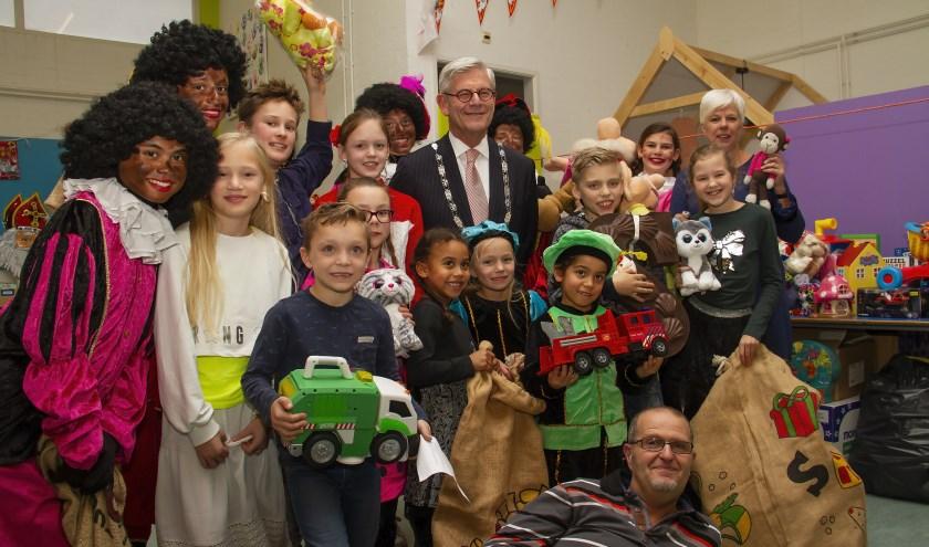 burgemeester met kinderen floriant, juf Hanneke Hoogeveen en liggend Ronald Offers van speelgoedbank IKROS.