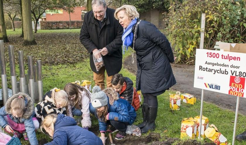 Burgemeester Annemiek Jetten kijkt samen met Wim Goedendorp belangstellend toe hoe de leerlingen de bloembollen planten bij het Mensenrechtenmonument.
